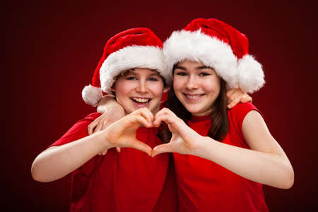 Christmas time - girl and boy with Santa Claus hat photo