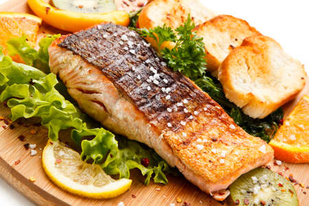 Grilled salmon with bread on a wooden board Stock Photo