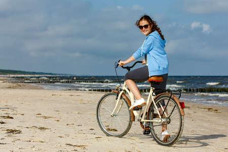 Teenage girl biking on beach