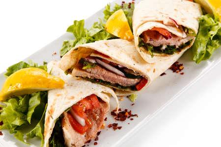 Lentebroodjes - wraps met vlees en groenten op een witte achtergrond Stockfoto