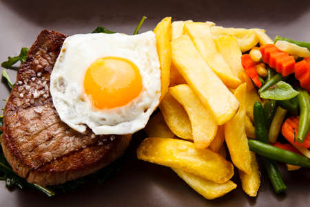 Grilled steak with french fries and fried egg