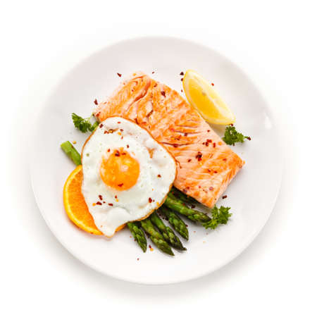 Grilled salmon with asparagus and fried egg on white background