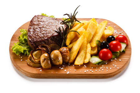 grill: Grilled beefsteak with french fries and mushrooms on a white background Stock Photo