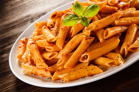 Pasta with tomato sauce on wooden table Stock Photo