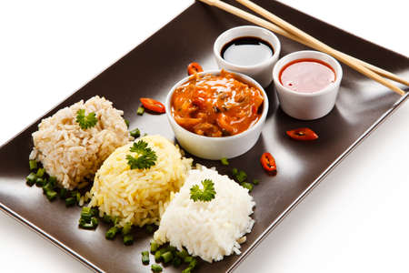 Rice dish with various sauces on white background