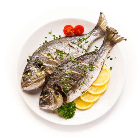 Fish dish - roast fish and vegetables on white background