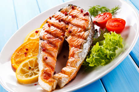 Grilled salmon with vegetables on a wooden table