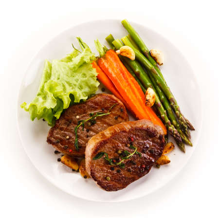 Grilled beef steaks with asparagus and carrots on white background Stock Photo