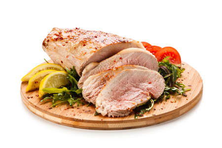 Roast ham with vegetables on wooden desk Stock Photo