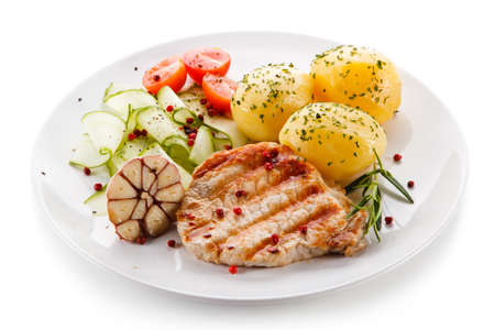 Grilled steak, boiled potatoes and vegetable salad on white background