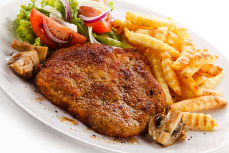 Fried pork chop, French fries and vegetable salad on white background