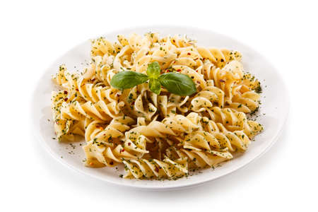 Pasta with herbs and basil on white background