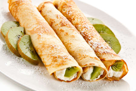 Crepes with kiwi and cream on white background Фото со стока
