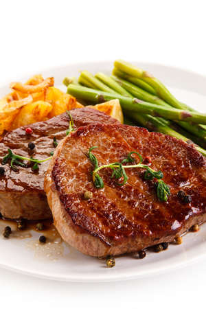 cutlets: Grilled beef steaks, chips and asparagus on white background