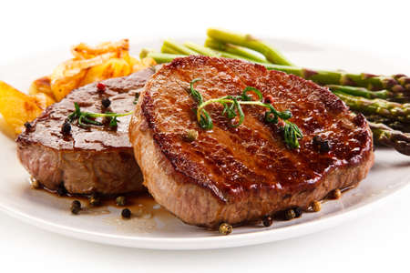 Grilled beef steaks, chips and asparagus on white background