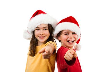 Tijd van Kerstmis - meisje en jongen met hoed van de Kerstman die OK teken Stockfoto