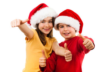 tradition: Christmas time - girl and boy with Santa Claus hat showing OK sign