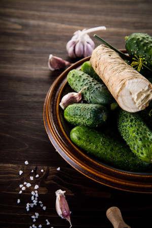 encurtidos: Raw cucumbers, garlic, horseradish and fennel on wooden background