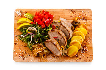 Roast steak with potatoes on cutting board