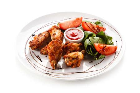 Grilled chicken drumsticks on white background