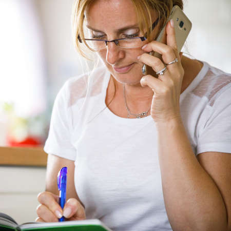 Middle-aged woman calling at home
