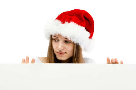 Beautiful woman in Santa Claus clothes peeking behind blank board on white background