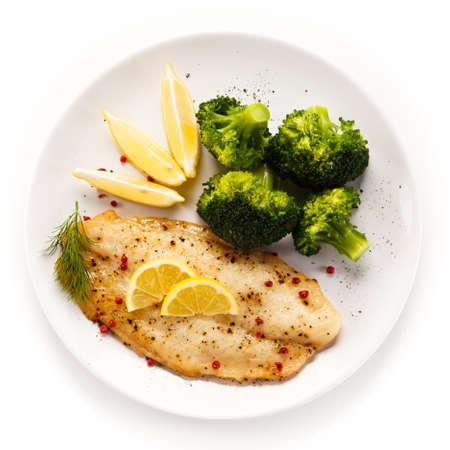 Filete de pescado frito con brócoli en el fondo blanco Foto de archivo - 89521985