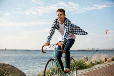 Young man biking on the beach