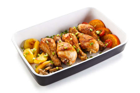 Roast chicken drumsticks and vegetables Stock Photo