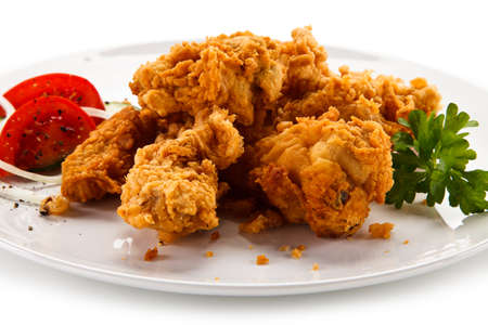 Fried chicken nuggets with vegetables on white background