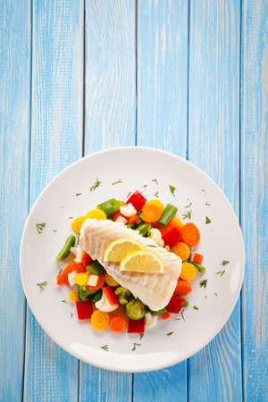Fish dish - fried fish fillet and vegetables on a blue wooden table