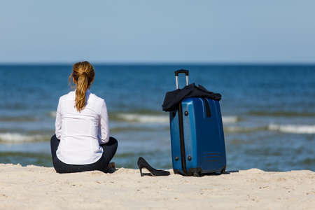 Businesswoman relaxing on beach beside the suitcase