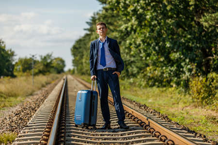 Businessman carrying suitcase on railway track