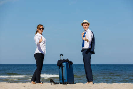 Woman and man relaxing on the beach with suitcase Stok Fotoğraf - 90419491