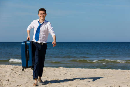 Businessman carrying suitcase on beach