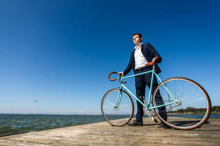 Young man standing with bike on pier