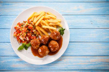 Gebraden gehaktballetjes, chips en groenten Stockfoto