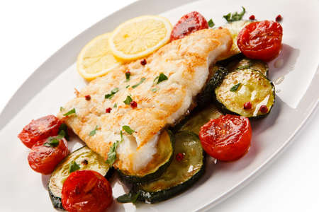 Fish dish - roast cod fillet and vegetables Stock Photo