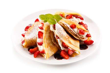 Crepes with strawberries and cream on white background Stock fotó