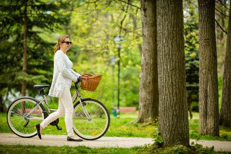 Urban biking - woman riding bike in city park Stock Photo