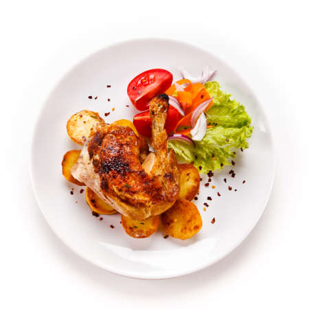 Roast chicken leg with chips on white background Stockfoto