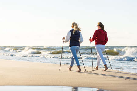 Nordic Walking - aktive Menschen arbeiten am Strand