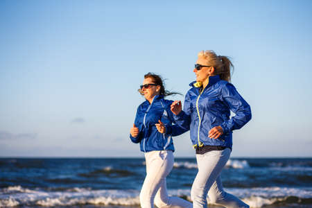 Middle-aged women running at seaside