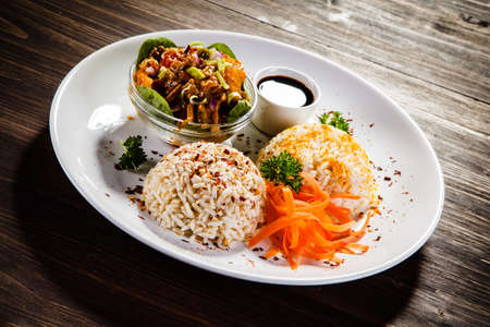 Rice dish with sauce on wooden background
