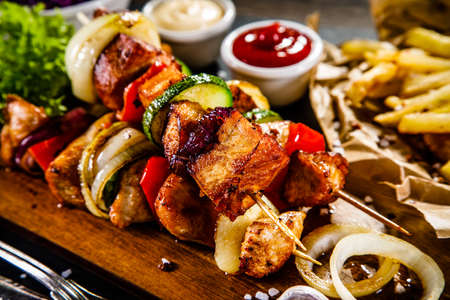 Kebabs - grilled meat with french fries and vegetables on wooden background Stockfoto