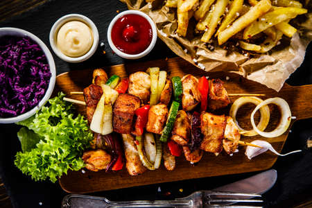 Kebabs - grilled meat with french fries and vegetables on wooden background Archivio Fotografico
