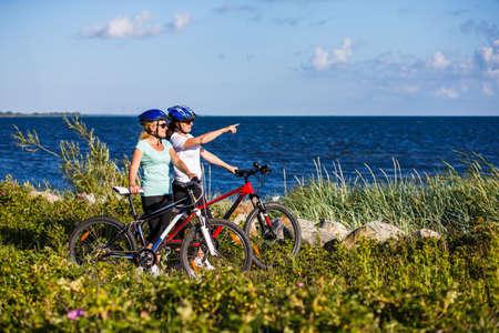 Women riding bicycles at seaside Stock Photo