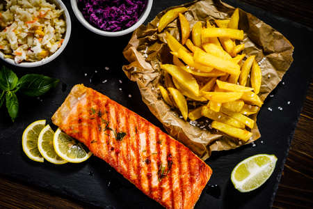Grilled salmon with french fries and vegetables served on a black stone plate