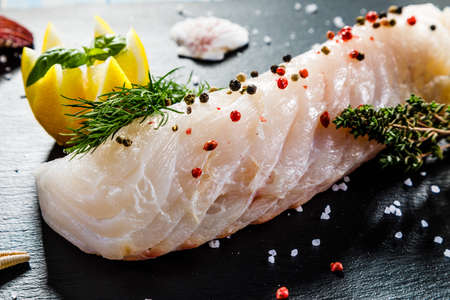 Fresh raw cod with herbs served on black stone