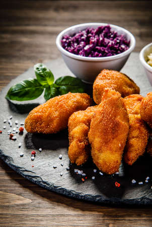 Fried chicken nuggets with cabbage served on black stone on wooden table